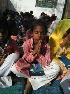 Kind sitzt mit gefalteten Händen am Boden und betet